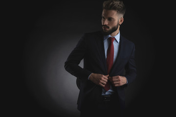portrait of curious businessman unbuttoning suit and looking to side