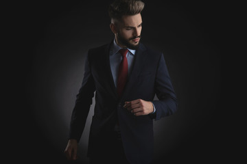 portrait of smart casual man in suit looking down to side