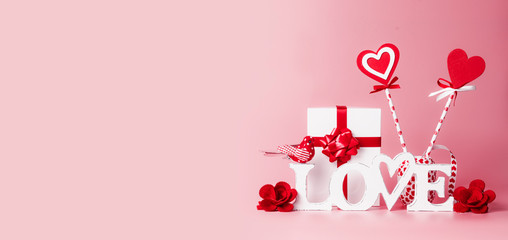 Valentines day background. Word Love, gift box, red ribbons and hearts lollipops. Festive greeting concept. Romantic Love declaration concept. Copy space for your design. Banner.
