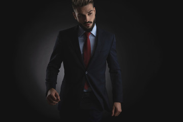 sexy businessman walks forward and looks down to side