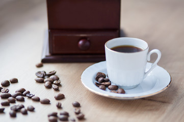 Cup of coffee close-up on a wooden background, coffee beans. Pleasant morning and cheerfulness