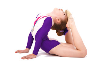 Little girl gymnast with a medal in a sports swimsuit doing exercises