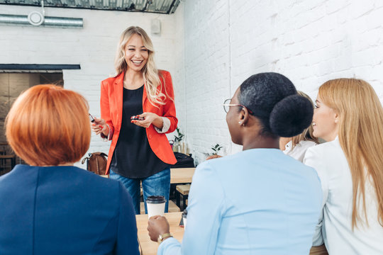 Attractive Female Sales Consultant in red jacket telling about new goods to young business women sitting in front of her at white interior office with take-away coffee. .