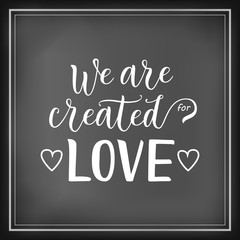 Modern calligraphy lettering of We are created for love in white on chalkboard background decorated with hearts and frame for decoration, poster, banner, valentine, valentines day, sticker, postcard