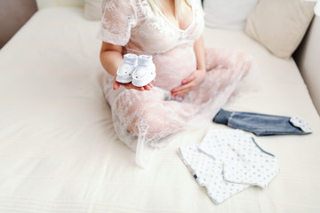 Close up of Caucasian pregnant woman holding baby's footwear in one hand while sitting on the bed with legs crossed. Other hand on tummy.