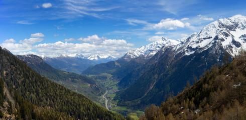 Fototapeta premium Piękna odgórnego widoku panorama wysokie śnieżyste góry i dolina z drogą i wioską w Szwajcaria przy wiosną