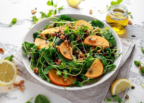 Persimmon and pea shoot salad with walnuts, pomegranate and pumpkin seed