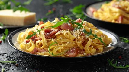 Classic Carbonara pasta, spaghetti with pancetta, bacon, egg, parmesan cheese and green arugula.