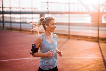 Beautiful young fit girl jogging on sunny summer morning.