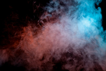 Translucent, thick smoke, illuminated by light against a dark background, divided into two colors: blue and red, burns out, evaporating from a pair of vape.