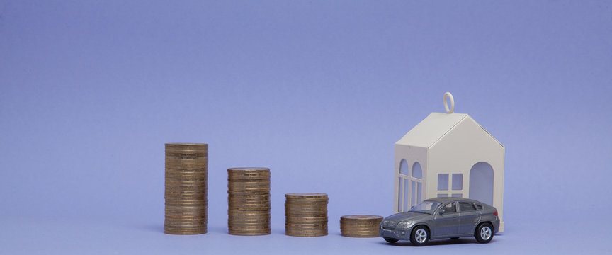 Gray car model and home with coins in the form of a histogram on a purple background. Concept of lending, savings, sale, lease of property