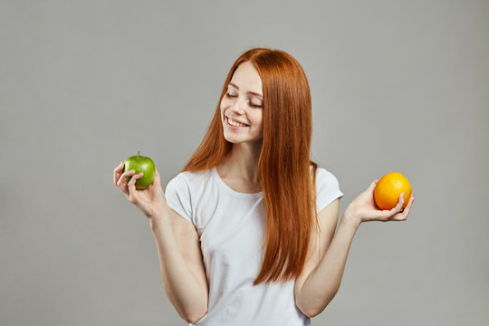 smiling cheerful girl comparing apple and orange. close up portrait. fresh fruit.