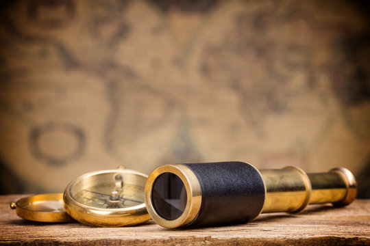 antique spyglass and compass on old map background
