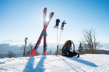 Skiing equipment - skis, backpack, sticks, gloves and action camera on monopod, on top of the ski slope at ski resort in the mountains