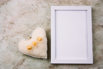 top view empty white wooden frame and fabric soft toy in a shape of heart