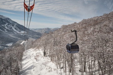 Flight of the camera over mountains. Aibga Ridge. Cable car with cabins go through the clouds. Mountains near the ski resort of Rosa Khutor in Krasnaya Polyana. Sochi.