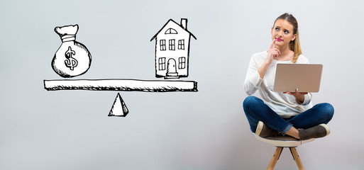 House and money on the scale with young woman using her laptop on a grey background