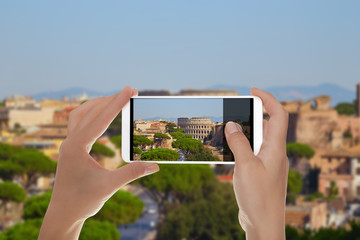 A tourist is making a photo of Rome cityscape with beautiful ancient Coliseum on a mobile phone