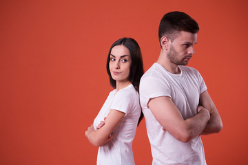 Close up photo of young angry and sad couple in white t-shirts with crossed arms and standing back to back on orange background