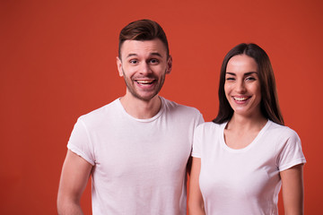 Happy and excited couple are posing in white t-shirts on orange background