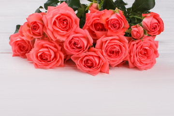 Bouquet of red blooming roses on white wooden table. Close up. Bunch of bright flowers.