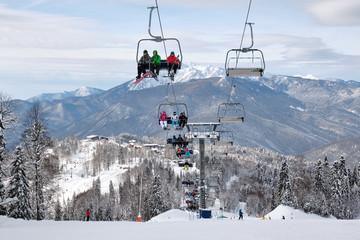 Fototapeta Open air ski lift going to the top of the mountain for alpine skiing. obraz
