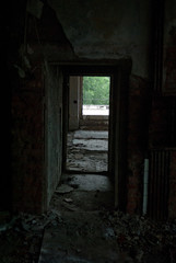Abandoned building, dark corridor, light in the doorway, ruins, broken windows, rust, unfinished