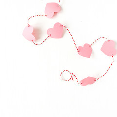 Valentine's Day composition. Heart symbol made of pink paper with rope on white background. Flat lay, top view.