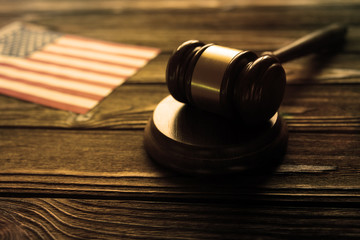 judge's hammer, American flag on wooden table background. law.