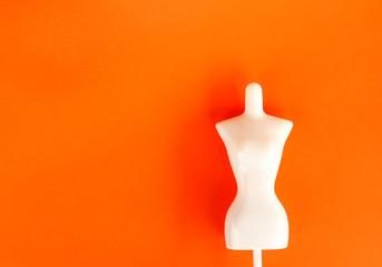 White plastic female mannequin figure on bright orange background