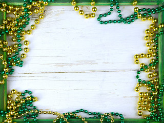 Image for Saint Patrick's Day on March 17th. Shiny green and gold beads on a wooden frame with rustic white washed wooden background. Copy space.