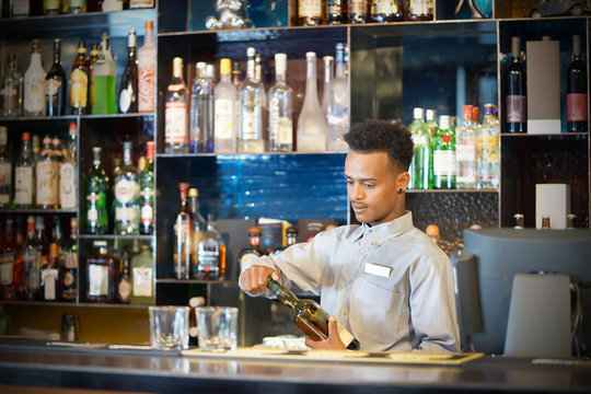 African bartender male pours whiskey to the client of the hotel bar. The concept of service. Focus on the bartender.