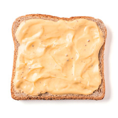 Bread slice with mustard sauce isolated on white, clipping path. Slice of multigrain bread square form plaster mustard sauce for toast. Image of one slice wholegrain bread, top view or flat lay.
