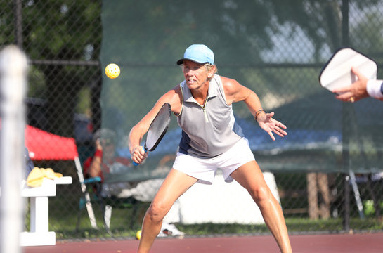 A woman competes in a pickleball match