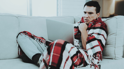 Man with Cold Sitting on Sofa in Checkered Blanket