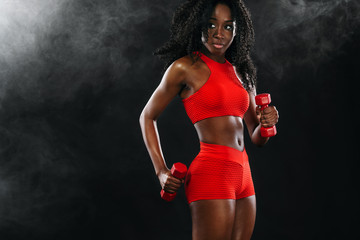 Sporty fit black skin woman in red sportswear, athlete with dumbbells makes fitness exercising on dark background.