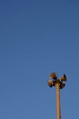 loudspeakers, speaker pole on blue sky background
