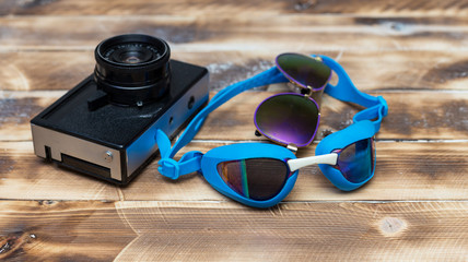 retro camera on a wooden table and swimming goggles