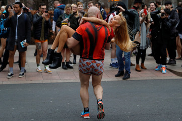 A couple in the No Trousers Tube Ride 2019 parade near fellow participants by the entrance to an underground station in London