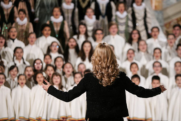 Back of a woman conducting a choir of children