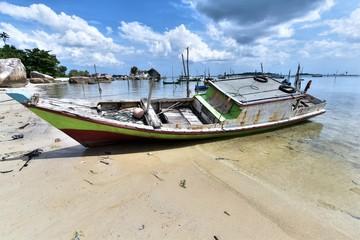 Weathered fishing boat lying on a sandy beach Pantai Tanjung Kelayang on the Island of Belitung, Indonesia