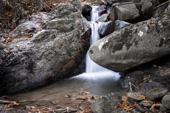 beautiful forest waterfall creek in long exposure in fall scenery