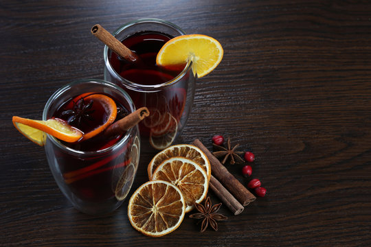 Glasses with mulled wine on brown background