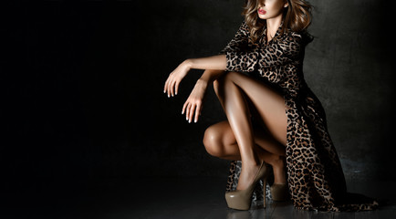 Beautiful sexy woman posing in Leopard print dress on dark