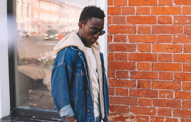 Wall Mural - Fashion african man wearing jeans jacket walking on city street, brick textured wall background
