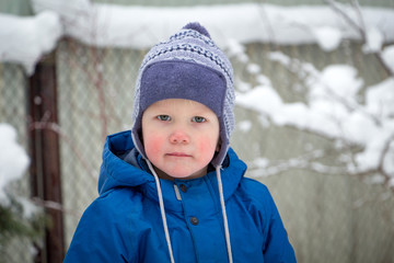 A little boy in a winter hat and jacket while walking on a cold winter snowy day