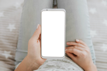 Mockup image of woman's hands. holding mobile phone white screen smartphone. top view. chroma key.