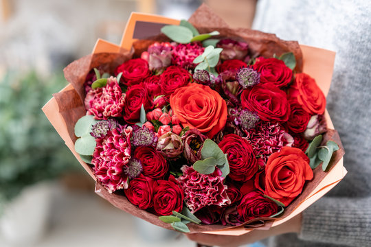 beautiful fresh cut bouquet of mixed flowers in woman hand. the work of the florist at a flower shop. Bright juicy red colors