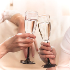 two hands holding glasses filled with champagne, wine, white wine, lemonade, clinking glasses, celebration