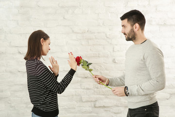 vPortrait of a young couple having conflict. Man asking for forgiveness offering a red rose flower to his offended girlfriend